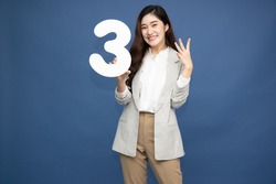 Young beautiful Asian woman showing number 3 and pointing up with finger number three isolated on blue background