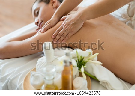 Young beautiful Asian woman sleep relaxing in the Oil spa massage in salon. Select focus hand of masseuse