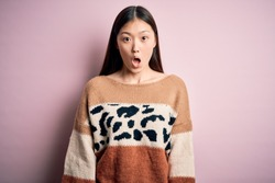 Young beautiful asian woman wearing animal print fashion sweater over pink isolated background afraid and shocked with surprise expression, fear and excited face.