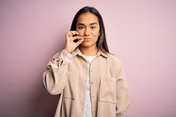 Young beautiful asian woman wearing casual shirt standing over pink background mouth and lips shut as zip with fingers. Secret and silent, taboo talking