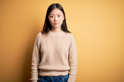 Young beautiful asian woman wearing casual sweater over yellow isolated background Relaxed with serious expression on face. Simple and natural looking at the camera.