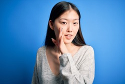 Young beautiful asian woman wearing casual sweater standing over blue isolated background hand on mouth telling secret rumor, whispering malicious talk conversation
