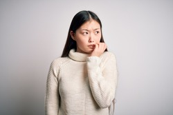 Young beautiful asian woman wearing casual sweater standing over isolated background looking stressed and nervous with hands on mouth biting nails. Anxiety problem.