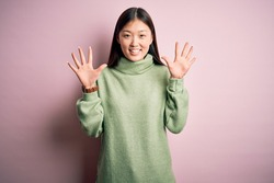 Young beautiful asian woman wearing green winter sweater over pink solated background showing and pointing up with fingers number ten while smiling confident and happy.