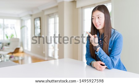 Young beautiful asian woman with long hair wearing denim jacket Pointing aside worried and nervous with forefinger, concerned and surprised expression