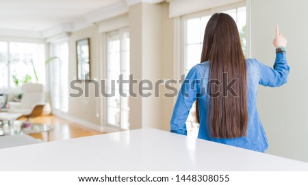 Young beautiful asian woman with long hair wearing denim jacket Posing backwards pointing ahead with finger hand