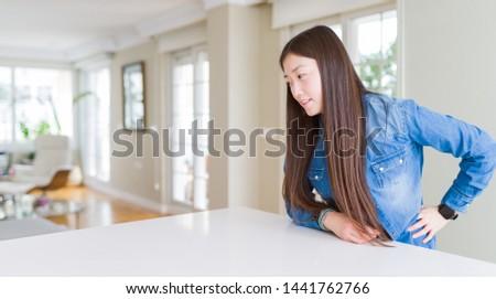 Young beautiful asian woman with long hair wearing denim jacket Suffering of backache, touching back with hand, muscular pain