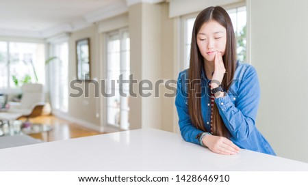 Young beautiful asian woman with long hair wearing denim jacket touching mouth with hand with painful expression because of toothache or dental illness on teeth. Dentist concept.