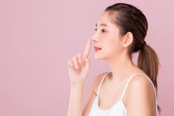 Young beautiful Asian woman with smiley face and red lips touching her nose, surgery nose job concept, isolated on pink background.