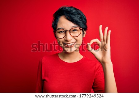 Young beautiful asian women wearing casual t-shirt and glasses over isolated red background smiling positive doing ok sign with hand and fingers. Successful expression. Photo stock ©