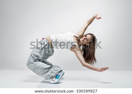 Young beautiful athletic girl dancing hip-hop in the studio.