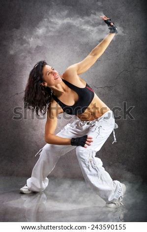 Young beautiful athletic woman dancing modern dance hip-hop on wall background with smoke