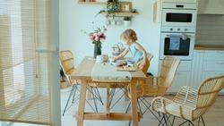 Young beautiful baby girl having fun in dining room.
