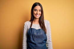 Young beautiful baker woman wearing apron uniform cooking over yellow background with a happy and cool smile on face. Lucky person.