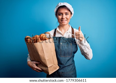 Young beautiful baker woman with blue eyes wearing apron holding paper bag with croissants happy with big smile doing ok sign, thumb up with fingers, excellent sign Stock fotó ©