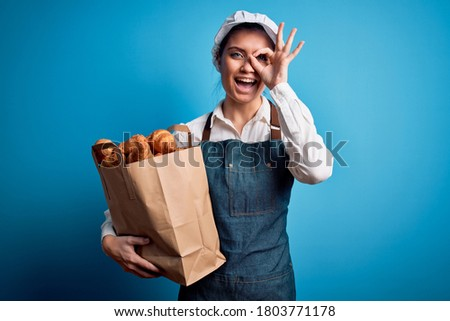 Young beautiful baker woman with blue eyes wearing apron holding paper bag with croissants with happy face smiling doing ok sign with hand on eye looking through fingers Stock fotó ©