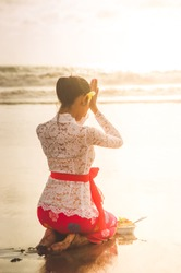 Young Beautiful Balinese Woman Pray on the Beach in Bali during Sunset with Traditional Bali Dress
