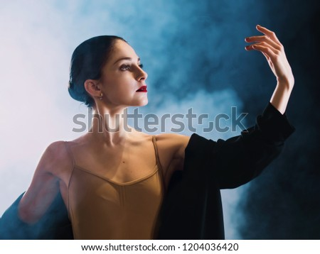 Young beautiful ballerina on smoke stage dancing modern ballet. performs smooth movements with hands. Woman in black costume on scene #1204036420