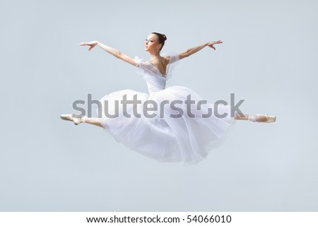 young beautiful ballerina posing in front of gray studio background
