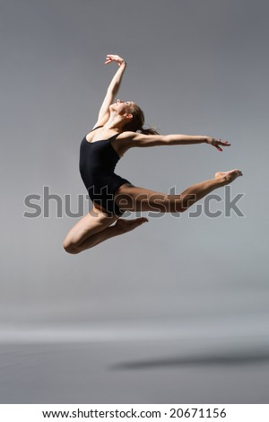 young beautiful ballerina posing on grey background