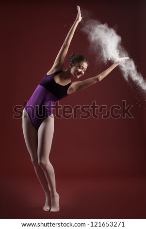 young beautiful ballerina with white dust in the hands of