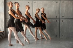 Young beautiful ballerinas in black dresses, young pantyhose and pointe shoes stand in one row and dance a ballet in the form of a black swan in a dark dance stage