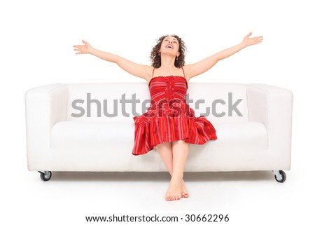 Young beautiful barefooted woman in red dress with hands up sits on white leather sofa