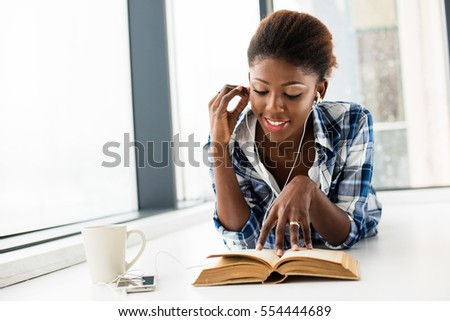 young beautiful black woman lying on the floor reading a book and listening music at her cellphone with a cup of coffee next