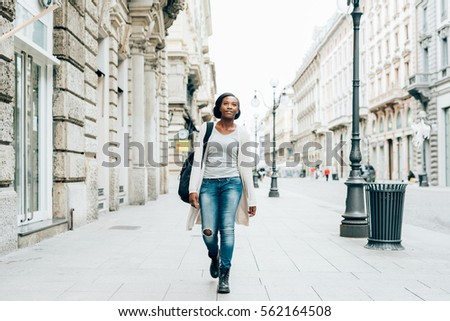 Young beautiful black woman outdoor in the city, looking at camera smiling wearing back pack - happiness, carefree, serene concept #562164508