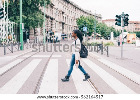 Young beautiful black woman outdoor in the city, looking at camera smiling wearing back pack - happiness, carefree, serene concept #562164517