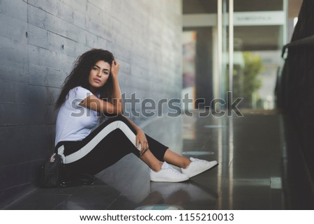 Young beautiful black woman with curly long hair sitting on the floor in urban place. Mixed girl wearing cute casual clothes looking at camera in a introspective pose.