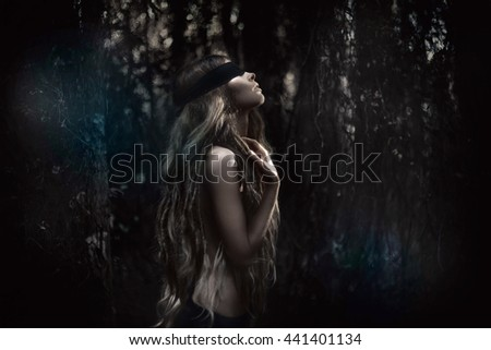 Young beautiful blindfolded woman in forest