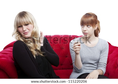 young beautiful blond and red haired girls is disgusting because of smoker on red sofa in front of white background