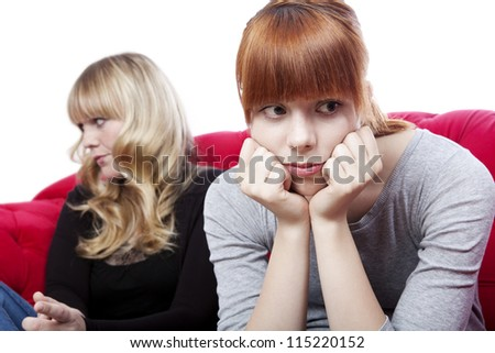 young beautiful blond and red haired girls sitting on red sofa and are sad and depressed in front of white background