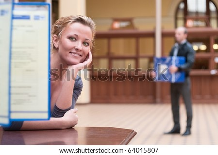 Young beautiful blond girl sitting at a table near the bar with the information and looks for