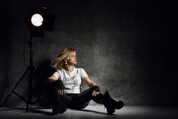 Young beautiful blond woman in stylish casual clothing and boots sitting on floor near light fixture over grey concrete background. Fashion and stylish headdress concept