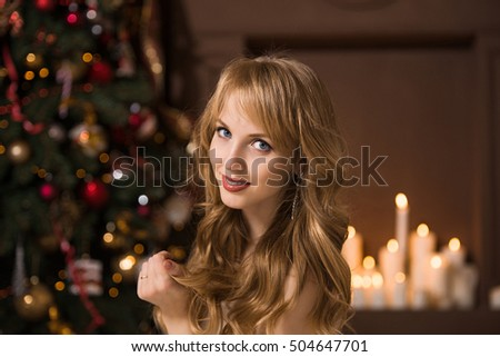 Young beautiful blond woman in the white dress on christmas with  perfect skin, woman in a beautiful room with a Christmas tree and candles, golden hair, happy woman new year, Redhead girl smiling #504647701