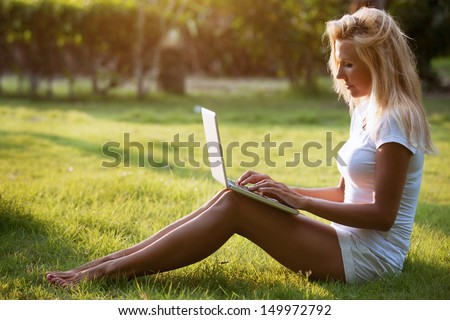 young beautiful blond woman sitting on the grass with the laptop - stock photo