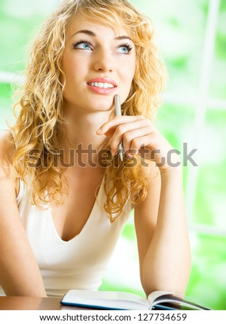 Young beautiful blond woman studying with notebook or organiser, indoors
