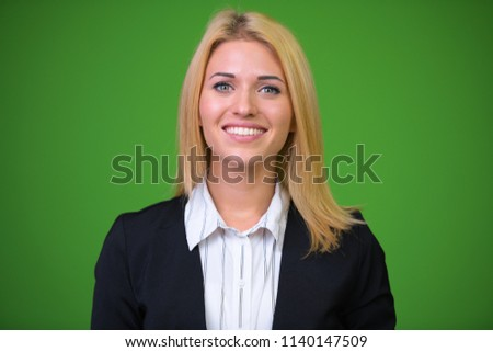 Young beautiful blonde businesswoman against green background stock photo