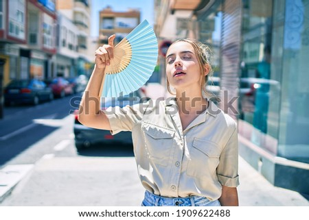 Young beautiful blonde caucasian woman smiling happy outdoors on a sunny day using handfan for hot weather
