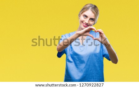 Young beautiful blonde doctor surgeon nurse woman over isolated background smiling in love showing heart symbol and shape with hands. Romantic concept.