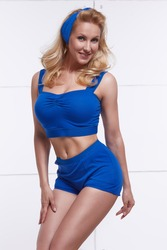 Young beautiful blonde dressed in style PinUp blue halter top and shorts and headband beautiful figure tanned body fitness sport