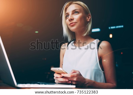 Young beautiful blonde female holding mobile phone while sitting with portable net-book in coffee shop interior, charming dreamy woman using cell telephone and laptop computer during rest in cafe #735122383