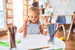 Young beautiful blonde girl kid enjoying play school with toys at kindergarten, smiling happy painting with pencil colors at home