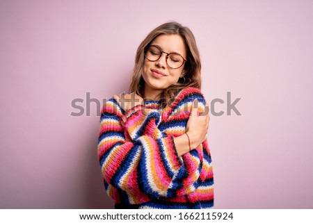 Young beautiful blonde girl wearing glasses and casual sweater over pink isolated background Hugging oneself happy and positive, smiling confident. Self love and self care Сток-фото ©