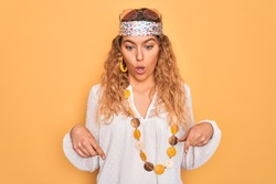 Young beautiful blonde hippie woman with blue eyes wearing sunglasses and accessories Pointing down with fingers showing advertisement, surprised face and open mouth