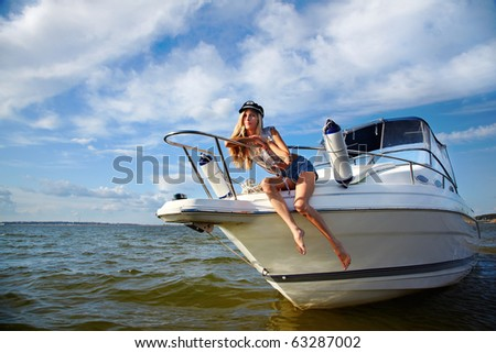 young beautiful blonde in captain's hat outdoors, posing on yacht #63287002