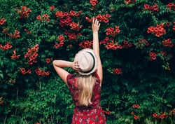 Young beautiful blonde long haired woman in red dress and straw hat standing backwards with raised hands over green natural background outdoor. Freedom happiness concept. Space for text.