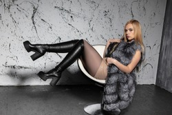 Young beautiful blonde posing sitting on a chair in the studio, dressed in a fur coat, blouse and shorts